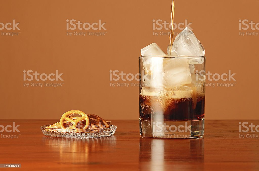Pouring coke in glass with ice cube and pretzel royalty-free stock photo