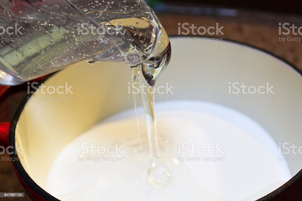 Pouring Corn Syrup into a Pot to Make Hard Candy stock photo