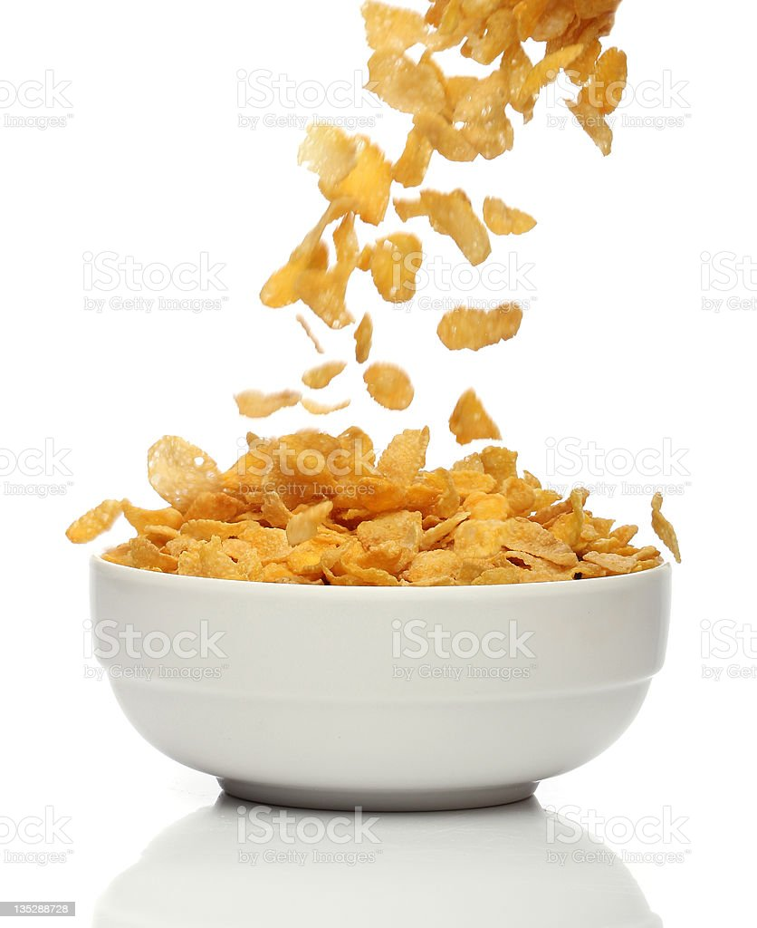 Pouring cornflakes into a bowl stock photo