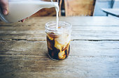 Pouring cream in cold brew coffee