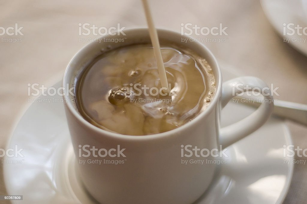 pouring cream into coffee royalty-free stock photo