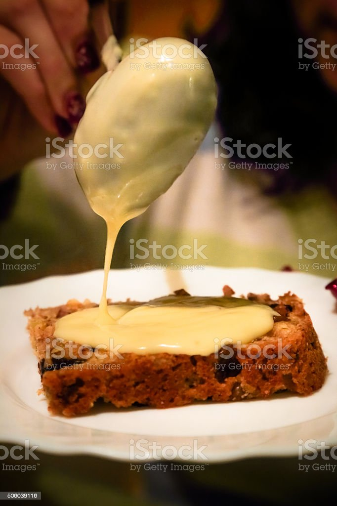 Pouring cream over a slice of Panettone (Italian Christmas cake) stock photo