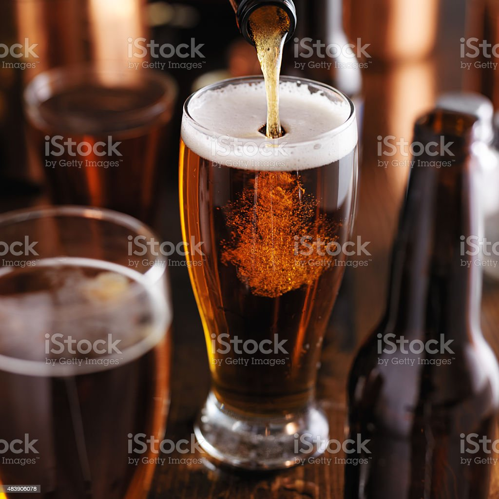 pouring dark stout beer stock photo