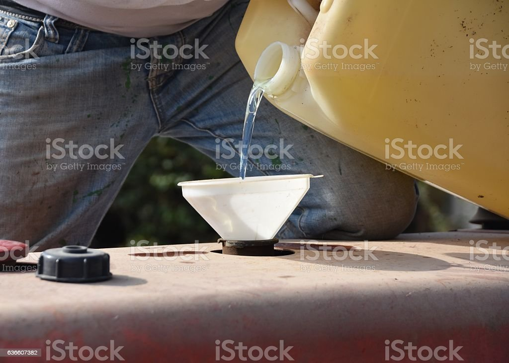 Pouring diesel into tractor stock photo