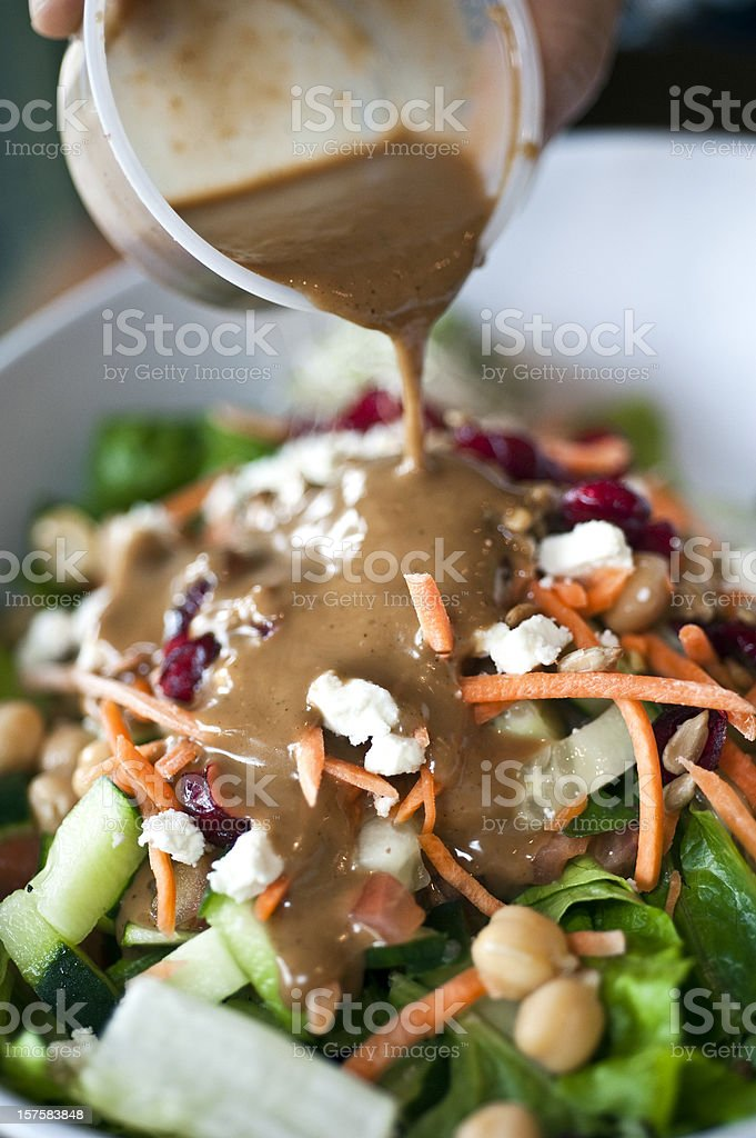 Pouring dressing over a salad stock photo