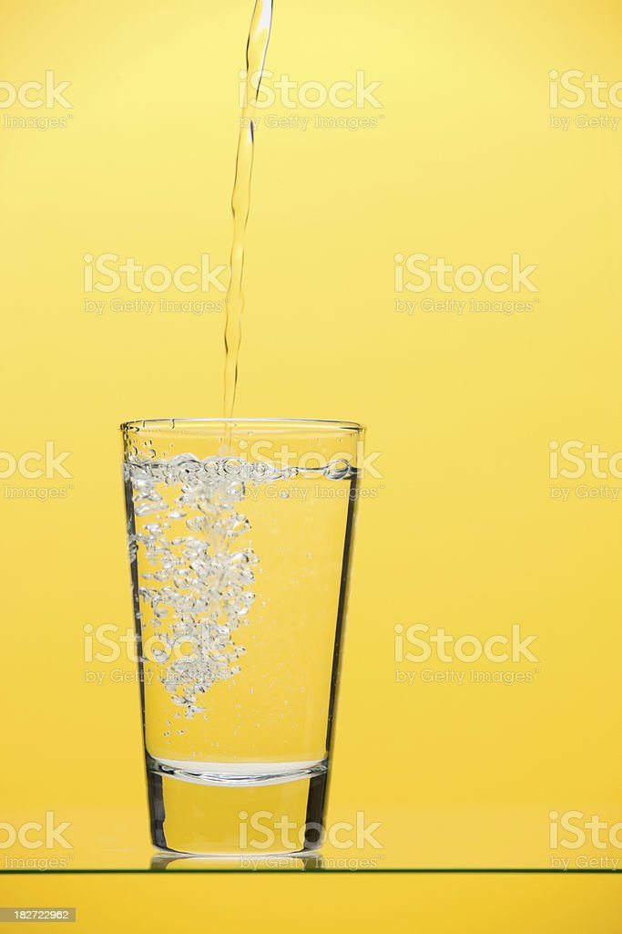 Pouring drinking water into glass on yellow royalty-free stock photo