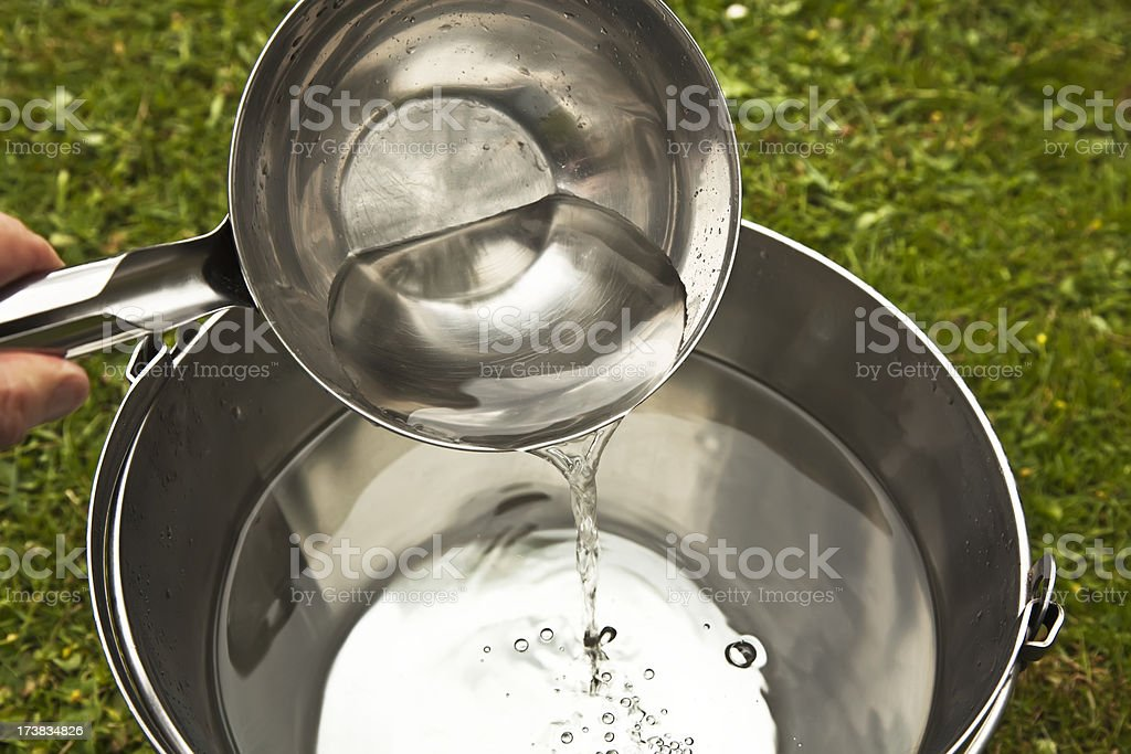 Pouring fresh water from ladle into a bucket. royalty-free stock photo