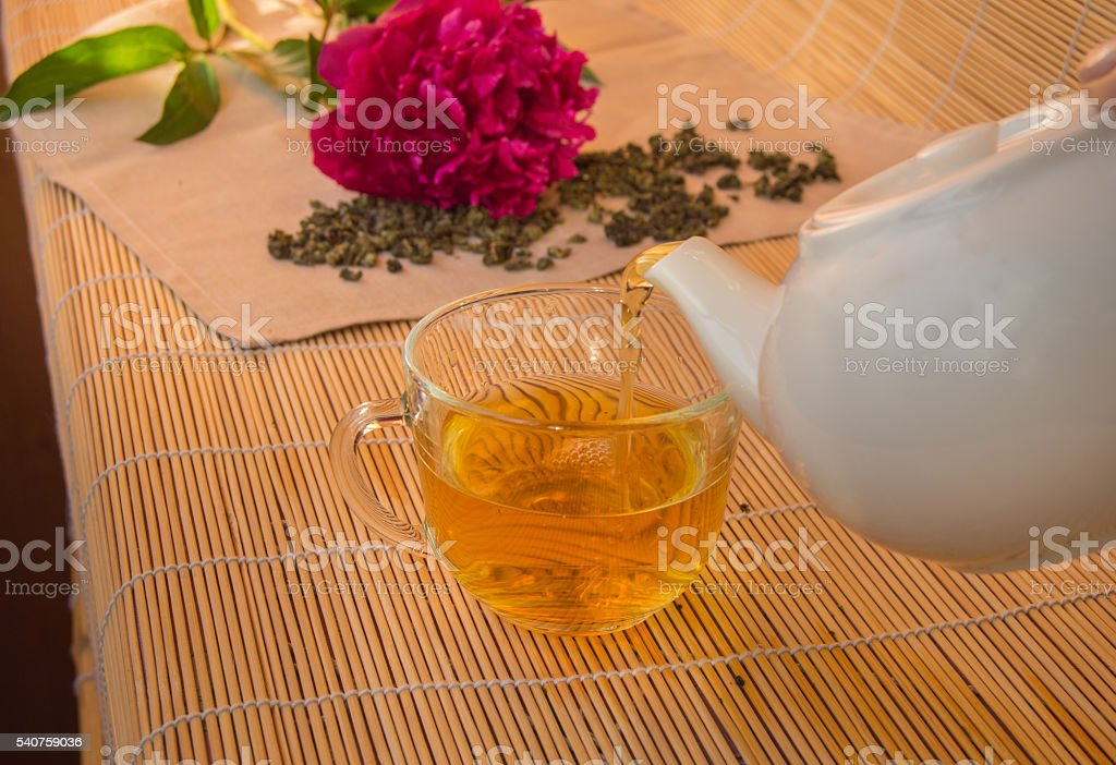 Pouring green tea from a white ceramic teapot in glass stock photo
