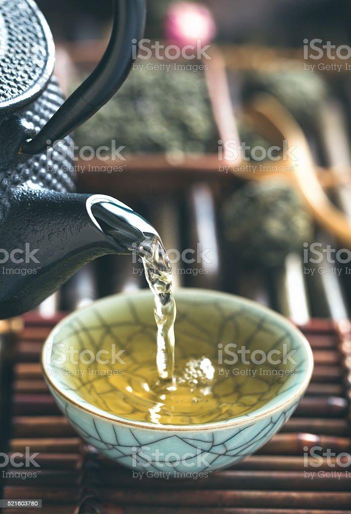 Pouring green tea vertical closeup stock photo