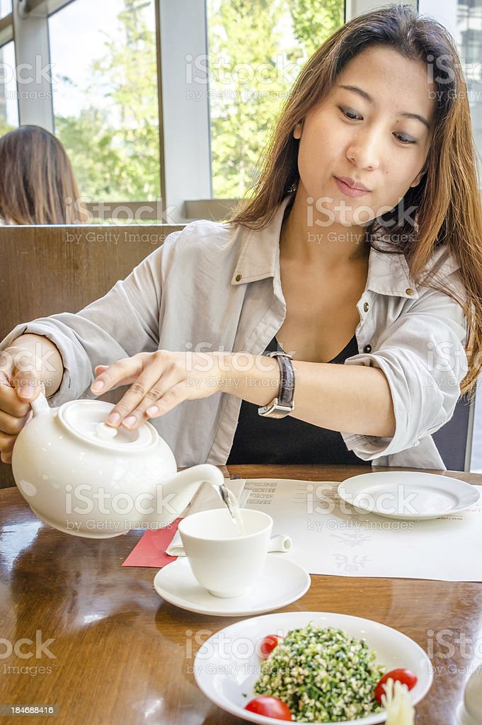 Pouring her tea royalty-free stock photo