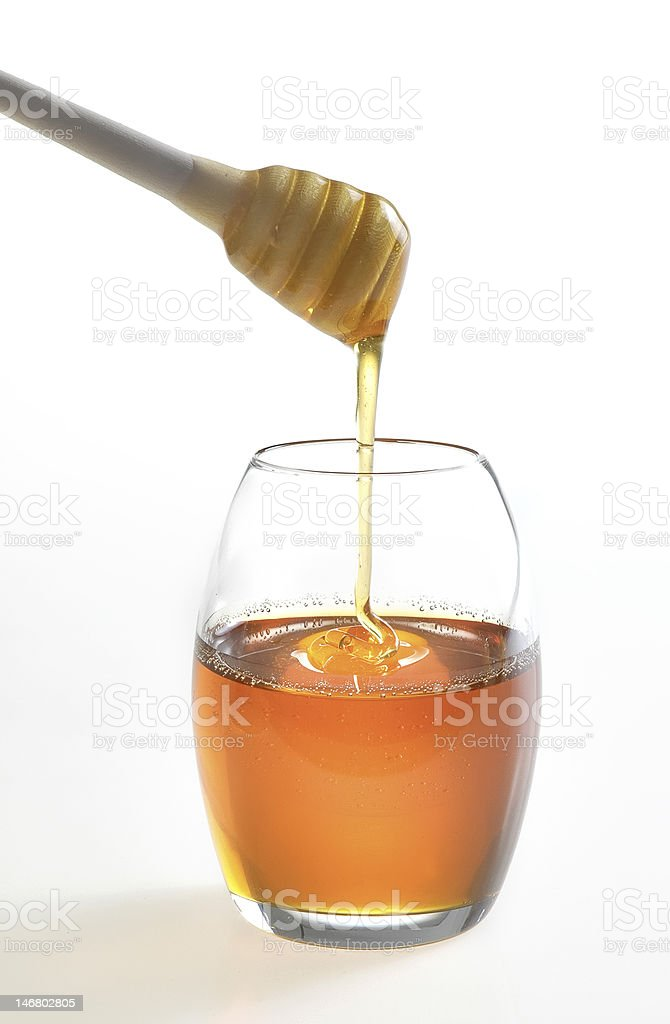 pouring honey in jar with wooden stick royalty-free stock photo
