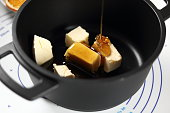 Pouring honey into saucepan with cubes of butter