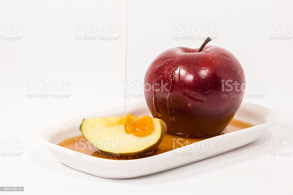 Pouring honey on red apple slice on white plate stock photo