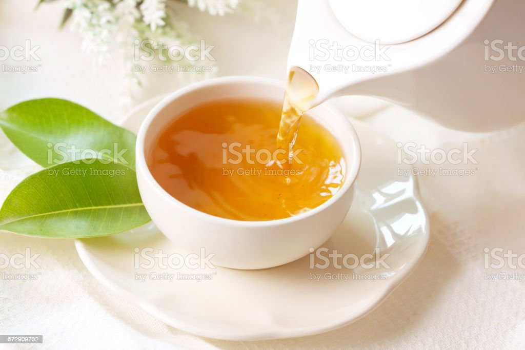 pouring hot black tea in a white tea cup stock photo
