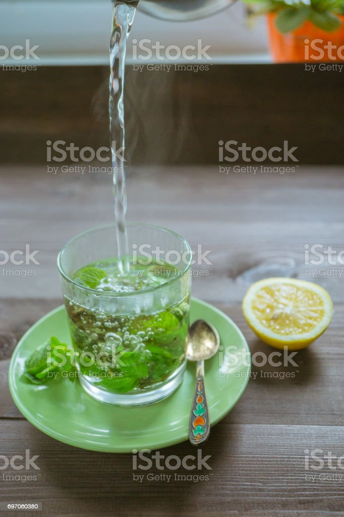 pouring hot water at the tea mug with mint and a lemon on a dark table stock photo