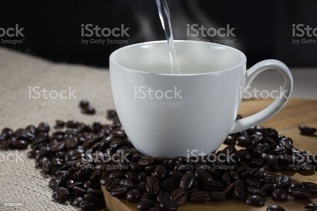 Pouring hot water into a cup of coffee royalty-free stock photo