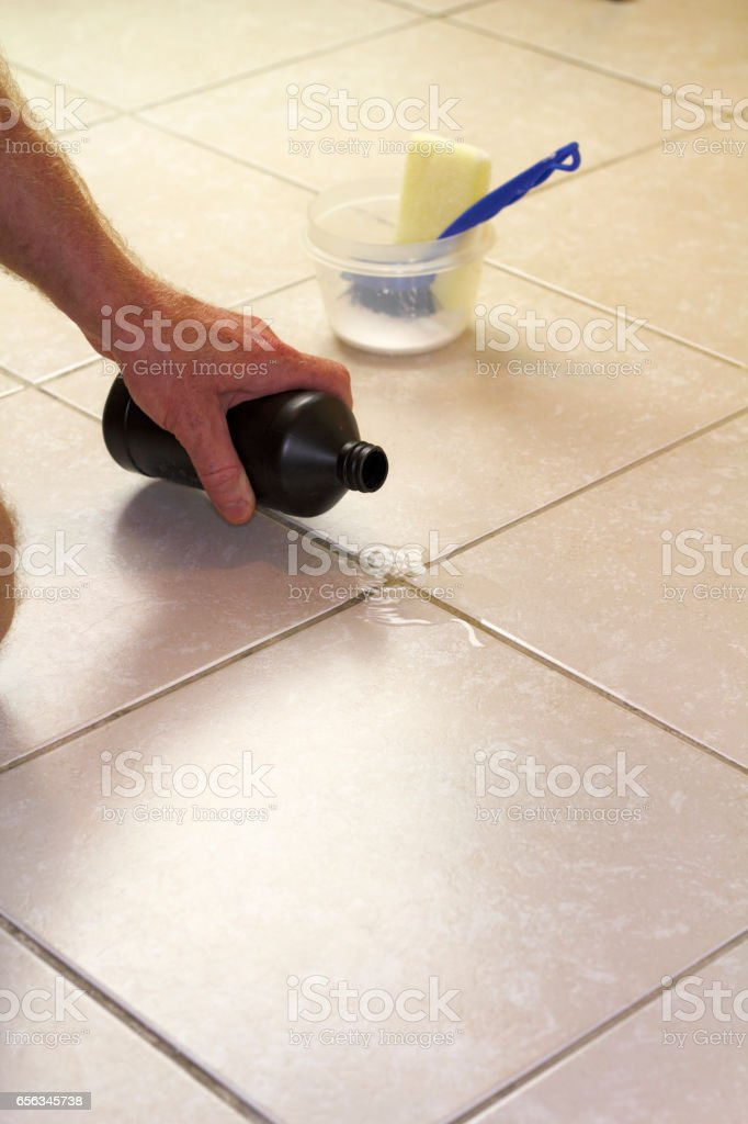 Pouring Hydrogen Peroxide on Floor Grout stock photo