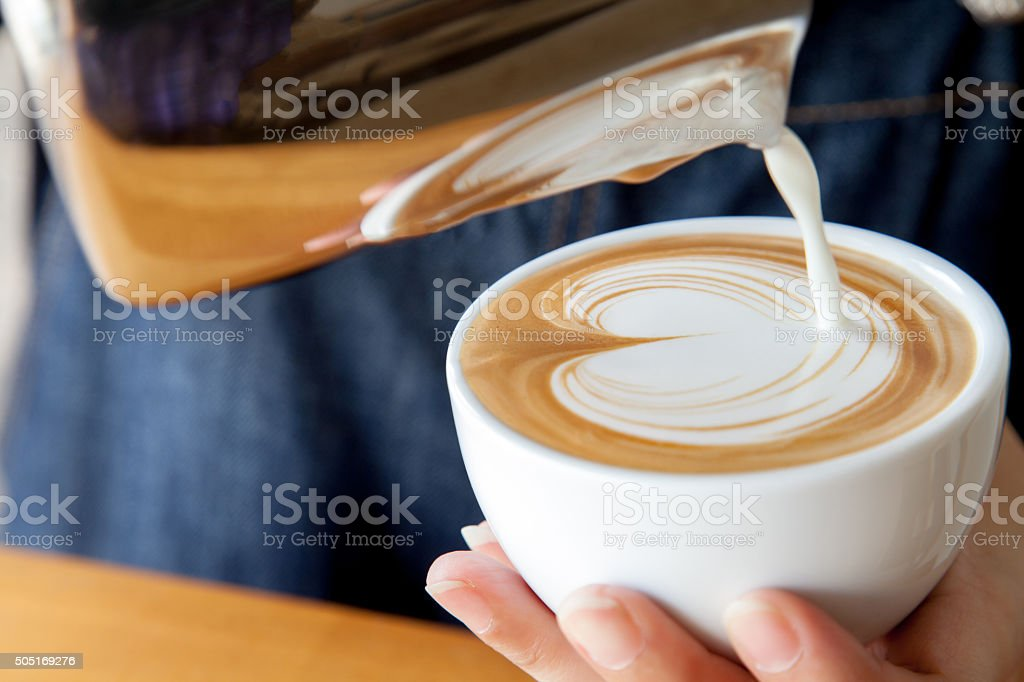 Pouring latte art into the cup stock photo