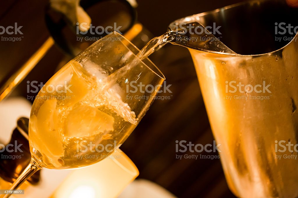 Pouring lemon flavored water into a wine glass royalty-free stock photo