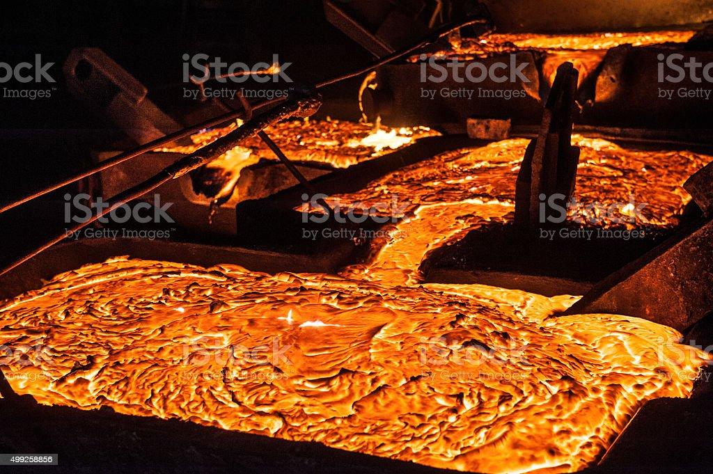 Pouring liquid titanium slag from arc furnace stock photo