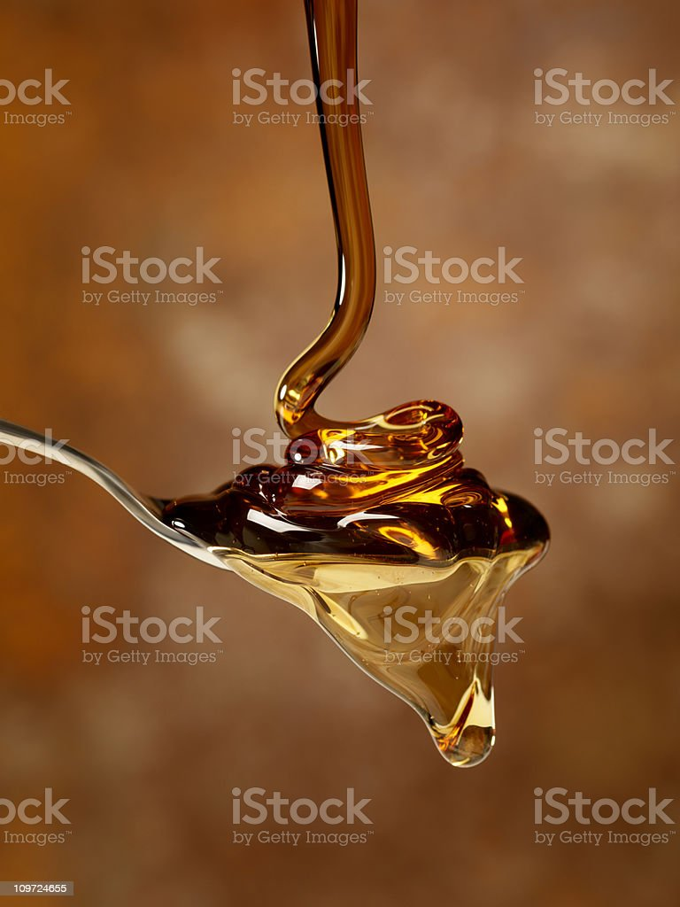 Pouring Maple Syrup over a Spoon stock photo