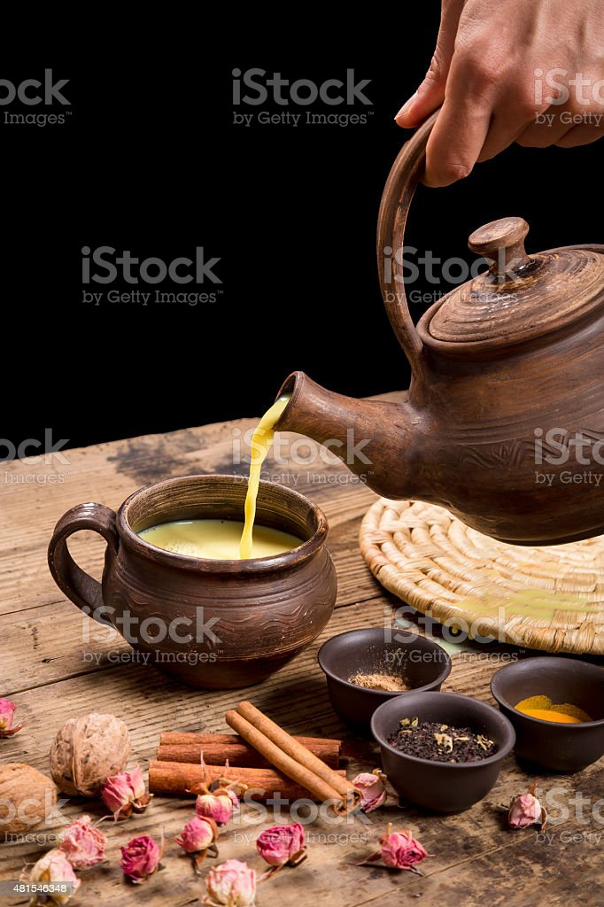 Pouring masala tea from pot stock photo