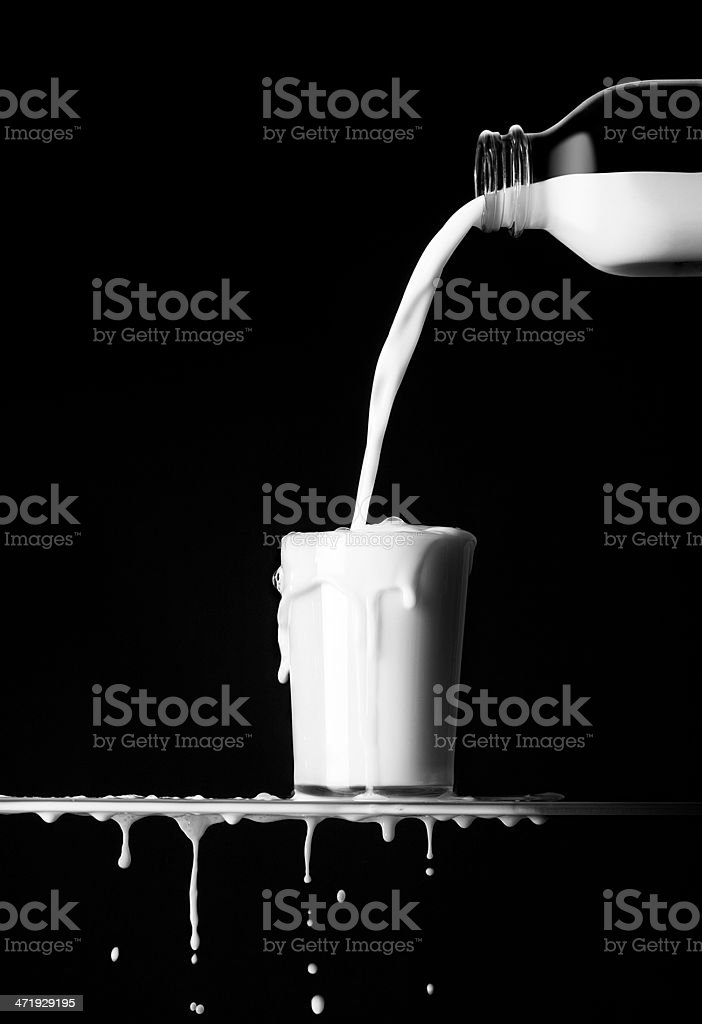 Pouring milk from a glass bottle into an overflowing cup stock photo