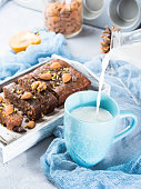 Pouring milk in blue mug for breakfast with cake. Vertical