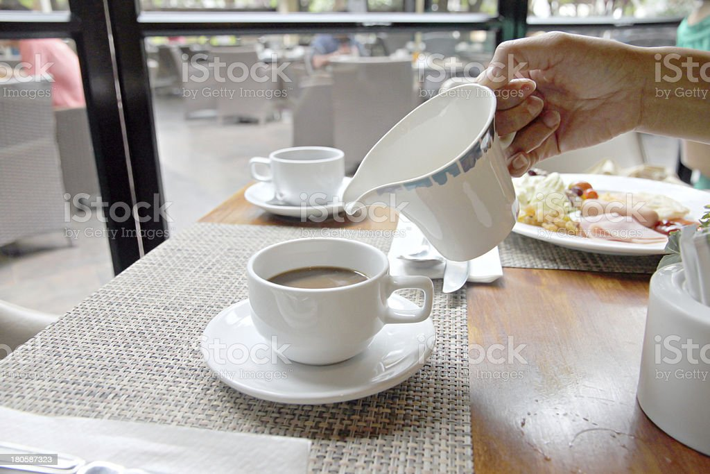 Pouring milk into coffee cup. royalty-free stock photo