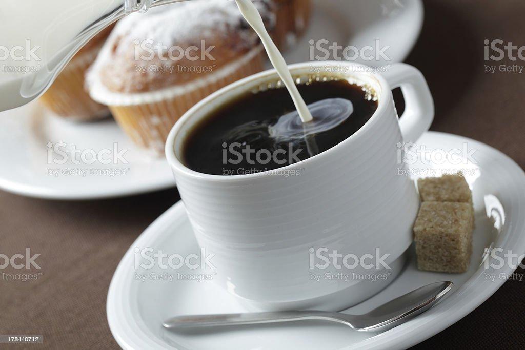 Pouring milk into coffee royalty-free stock photo