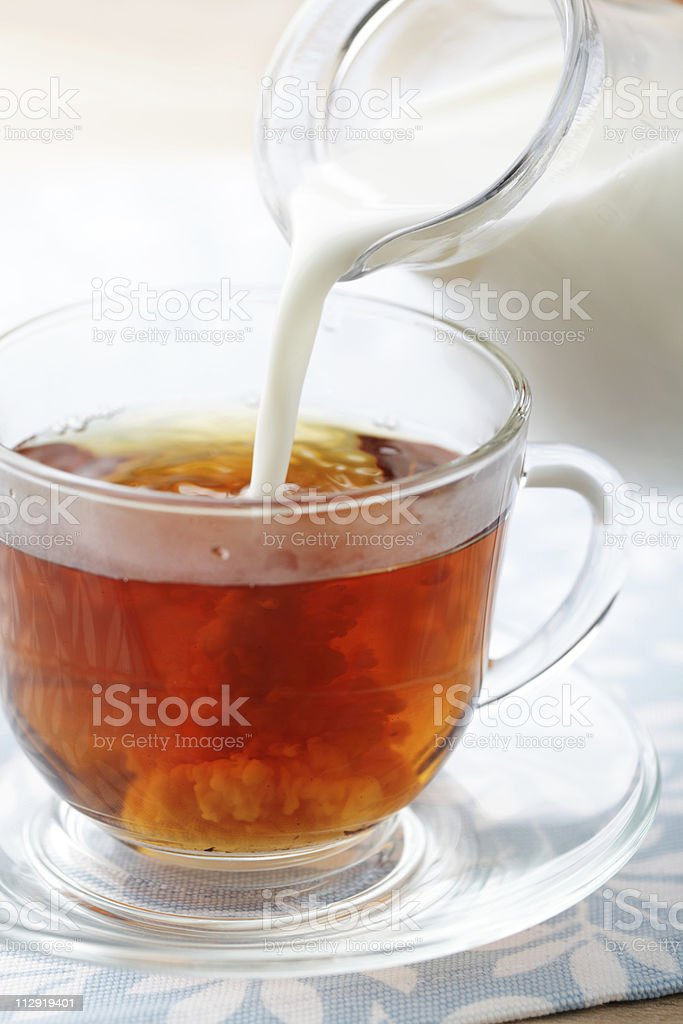 Pouring milk into cup with tea stock photo