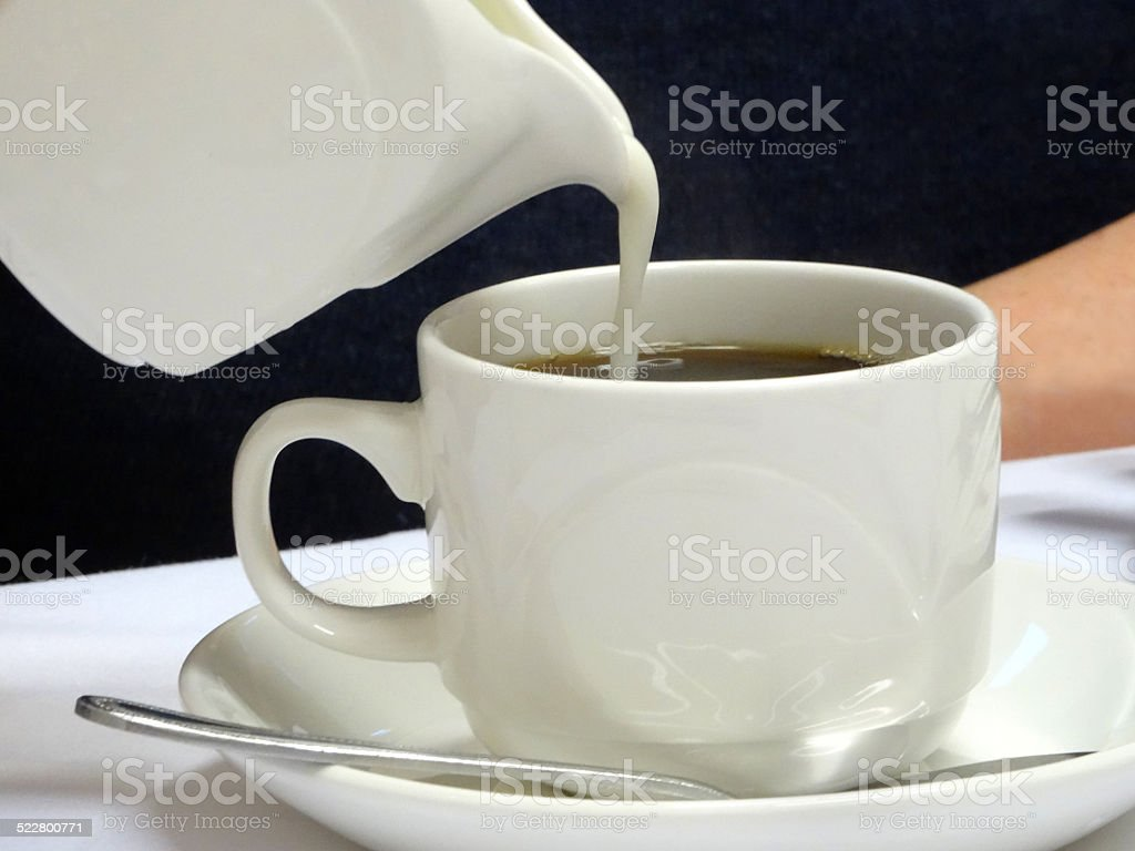 Pouring milk into cut of black coffee, white china jug stock photo