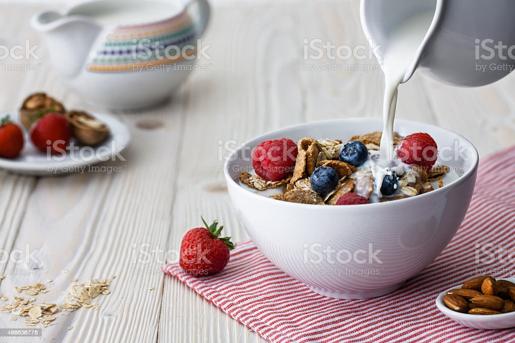Pouring milk into the bowl with flakes stock photo