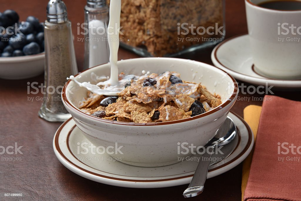Pouring milk onto cereal stock photo
