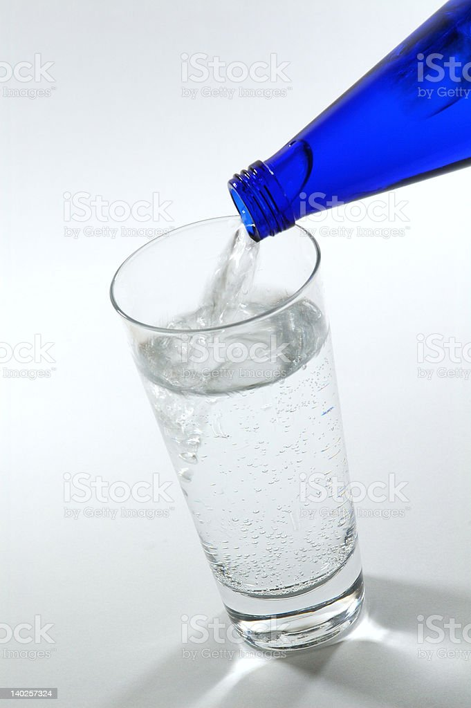 Pouring Mineral Water into a Glass from Blue Bottle stock photo