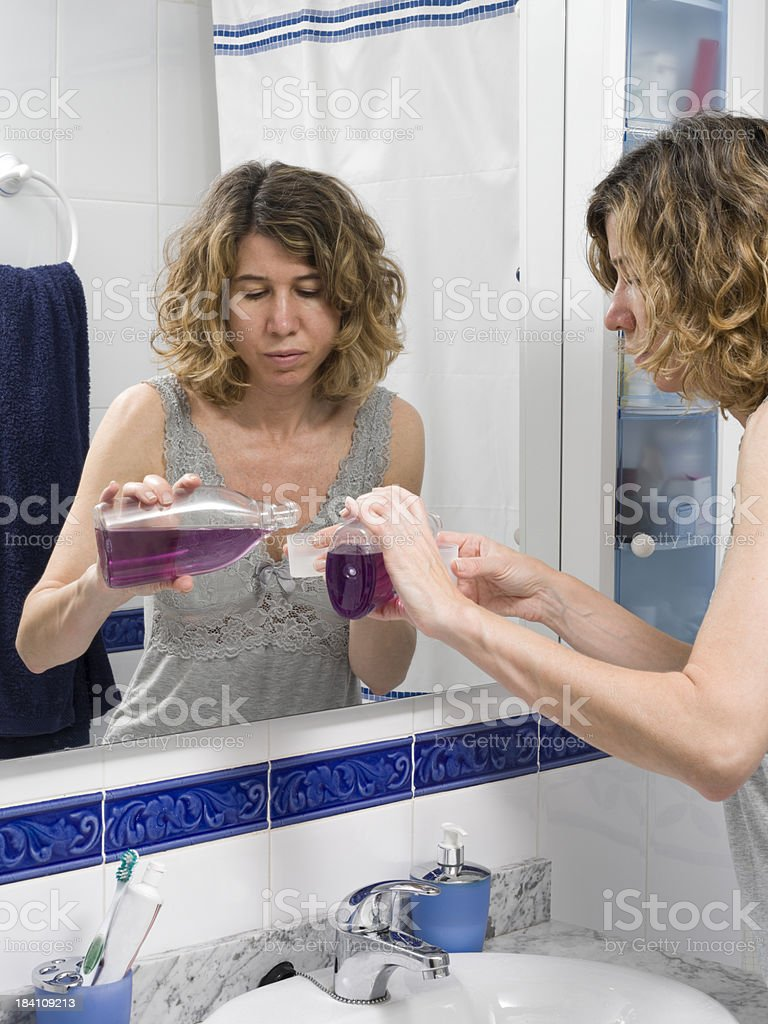 Pouring mouthwash in a cup stock photo