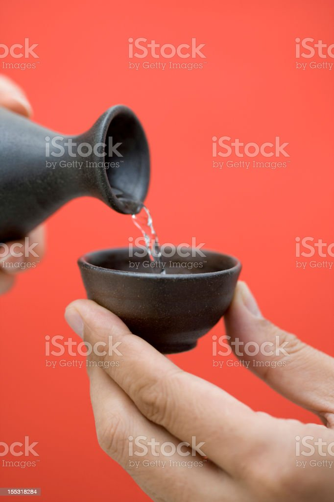 Pouring of sake from a jug to a cup stock photo
