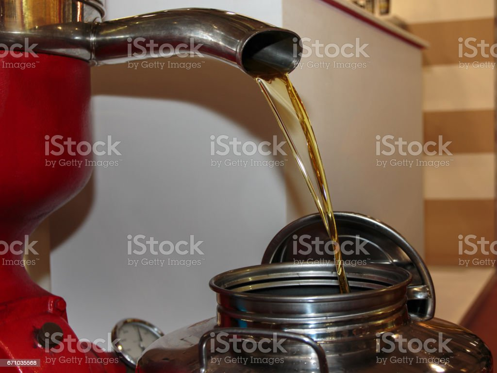 Pouring Oil from Steel Pipe: Closeup View of Olive Oil Mill stock photo