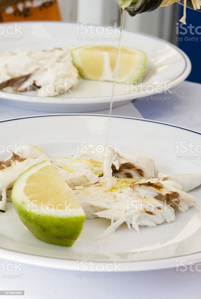 Pouring Olive Oil Down to Roasted Fish royalty-free stock photo
