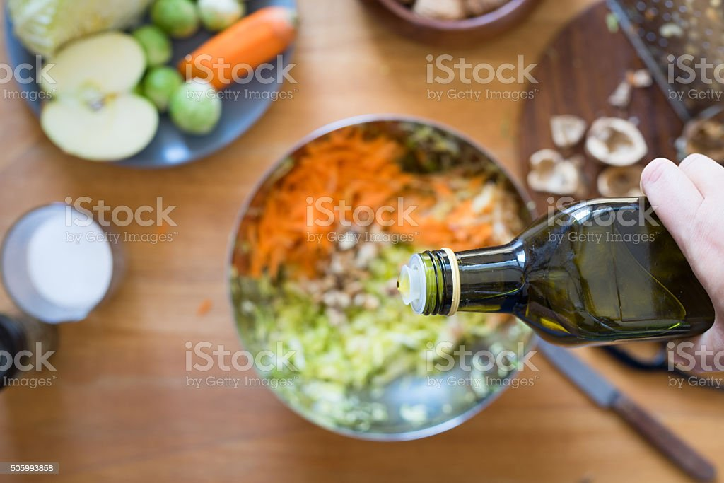 Pouring olive oil from bottle onto salad stock photo