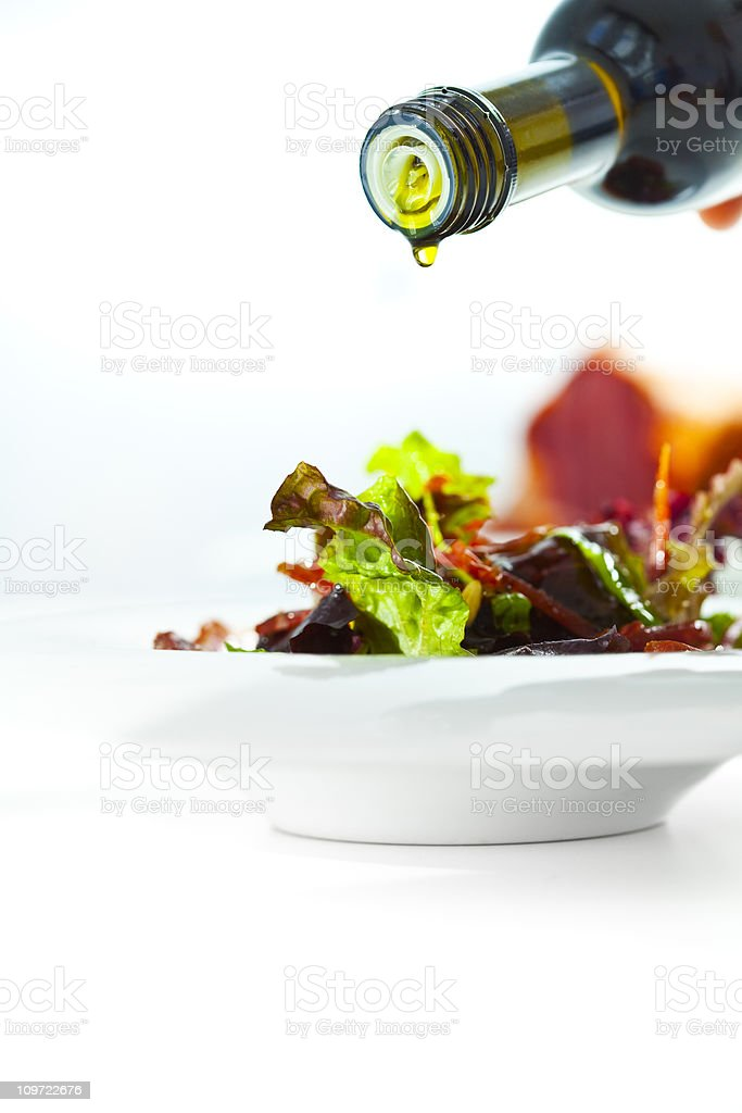 Pouring olive oil on fresh salad royalty-free stock photo