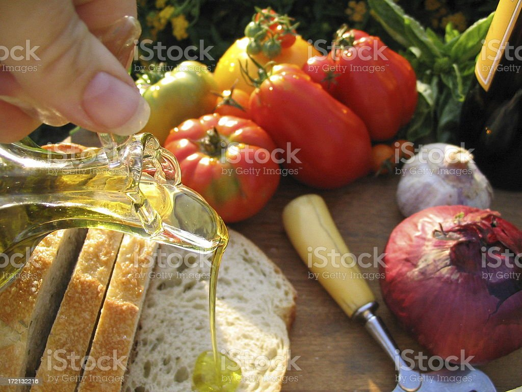 Pouring Olive Oil on Sandwich Bread, Wine Picnic, Heirloom Tomatoes royalty-free stock photo