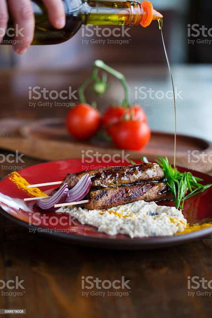 Pouring olive oil over kebab stock photo