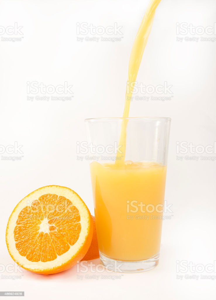 Pouring Orange Juice into Glass with Orange Halves stock photo