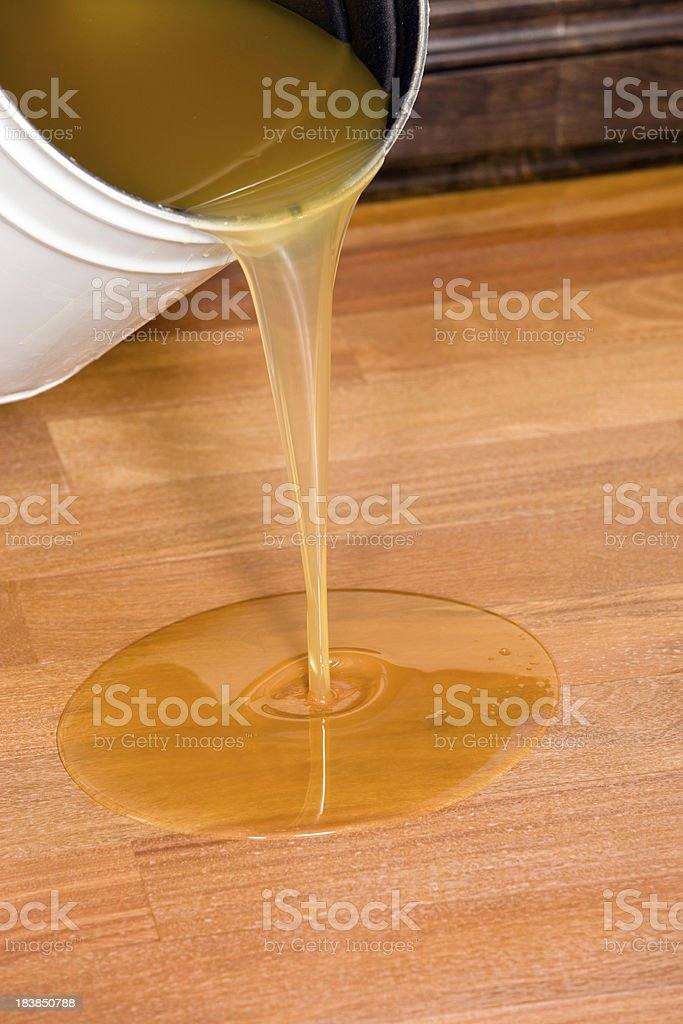 Pouring Polyurethane Clear Coat on Hardwood Floor stock photo