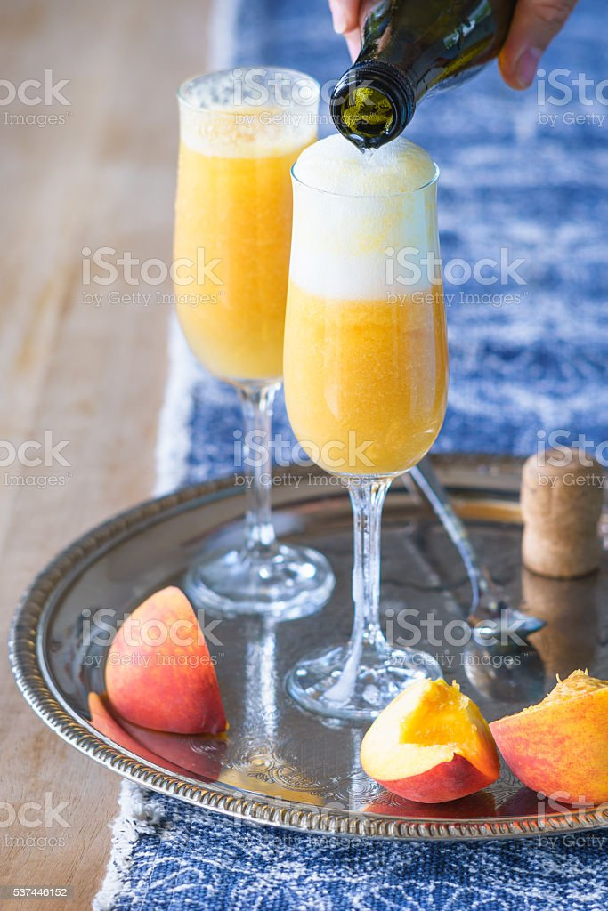 Pouring Prosecco wine to pureed peach to make Bellini cocktail stock photo
