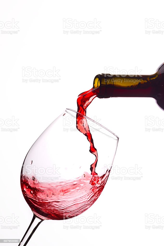 Pouring red wine from a bottle stock photo