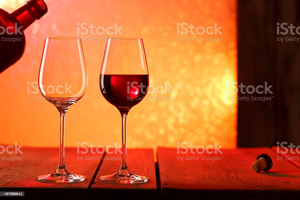 Pouring red wine from an elegant bottle into stylish wineglass stock photo