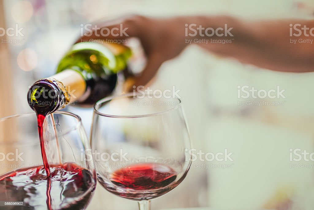 Pouring red wine in glasses stock photo