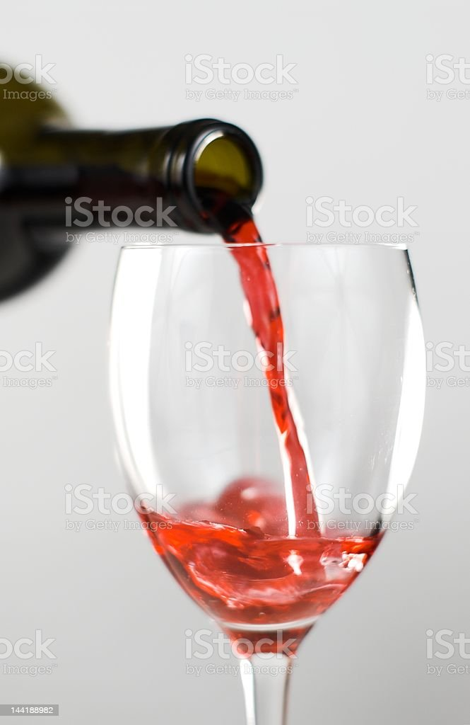 Pouring red wine into a glass royalty-free stock photo